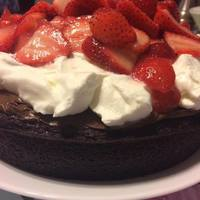 Decadent Chocolate Fudge Cake with Whipped Cream and Fresh Strawberries