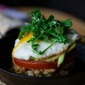Farro Cake topped with Tomato, Avocado, Egg, and Arugula Salad